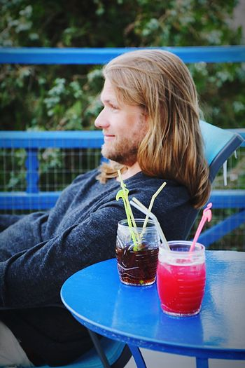 Side view of smiling man with drinks on table