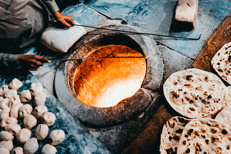 High angle view of man preparing nan bread