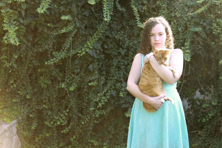 Portrait of young woman holding cat while standing against plants in park