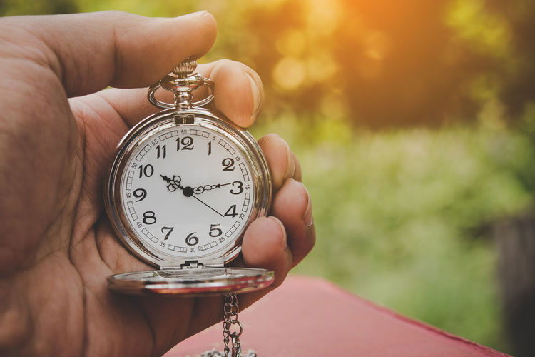 Close-up of hand holding pocket watch outdoors