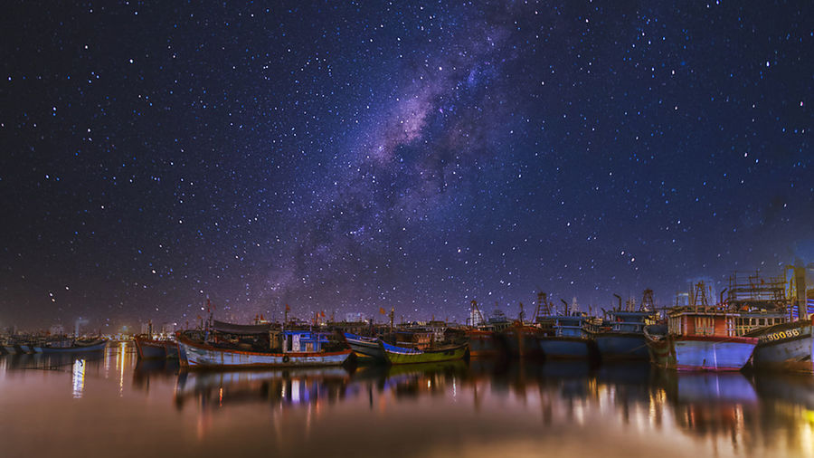 Panoramic view of illuminated canal against sky at night