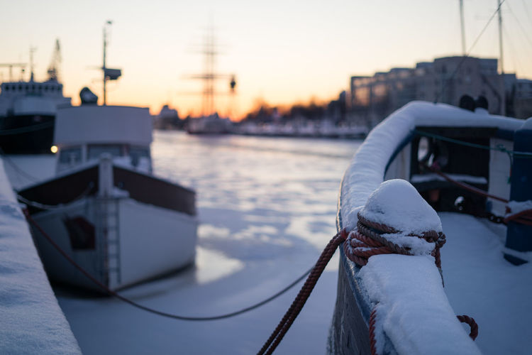 Snow covered boats on aura river at winter sunset