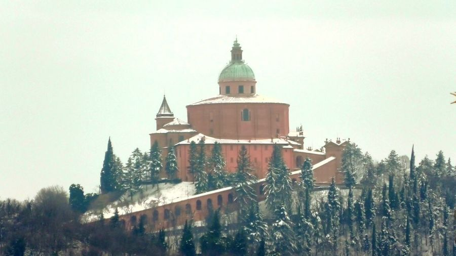 distant close up of snowy San Luca basilica in a winter morning on Bologna hills in Italy. Bologna Bologna, Italy Italy San Luca San Luca's Church San Luca Bologna San Luca Skyline Church Cathedral Basilica Night Sunset Religion Dome Madonna Holy Mary Holy Virgin Madonna Di San Luca Dawn Snow Snowy Winter Building Exterior Architecture Built Structure Tree Sky Building Nature Plant Place Of Worship Belief Day Spirituality Clear Sky Cold Temperature No People Tower Outdoors Spire
