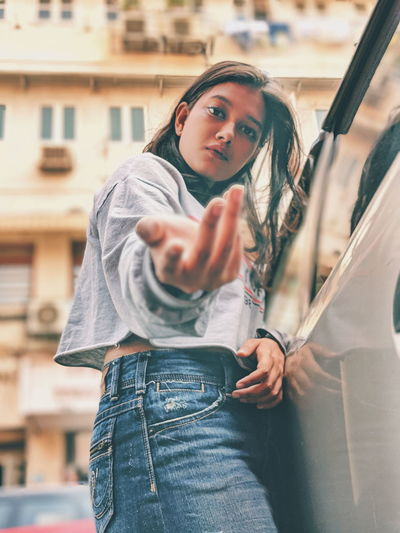 Low angle portrait of young woman gesturing while standing against building in city