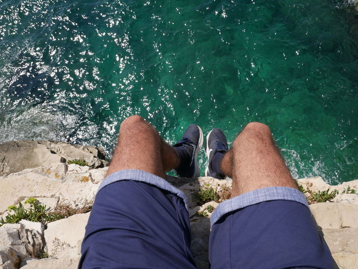 Low section of man legs against sea