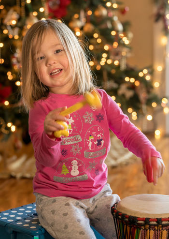 Happy preschool toddler with christmas gifts and presents and playing on an african drum Christmas Drum Drummer Happy Music Preschool Age Presents Tree Xmas Celebration Child Childhood Cute Drumming Gift Girl Looking At Camera Parcel Portrait Pretty Real People Smiling Toddler  Unwrapping