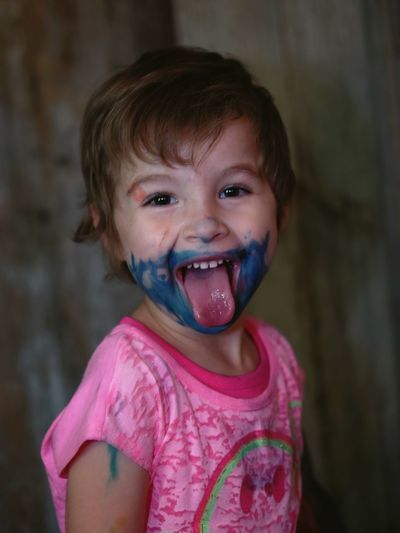 Portrait of cute girl with face paint sticking out tongue