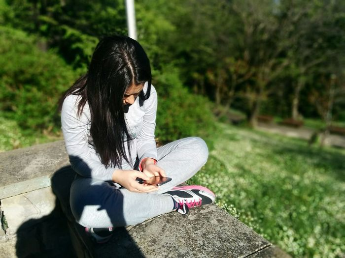 Woman using phone while sitting on resting wall against trees