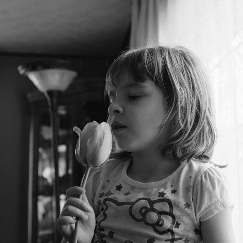 Girl holding tulip at home
