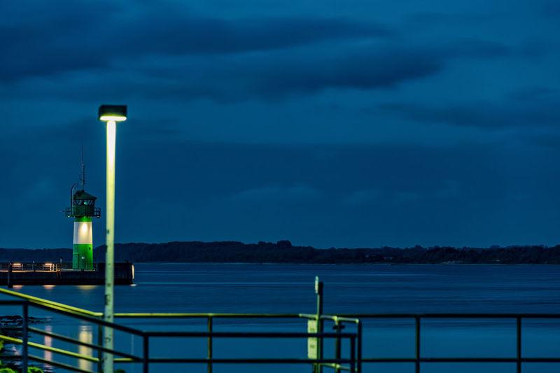 Illuminated railing by sea against sky at dusk