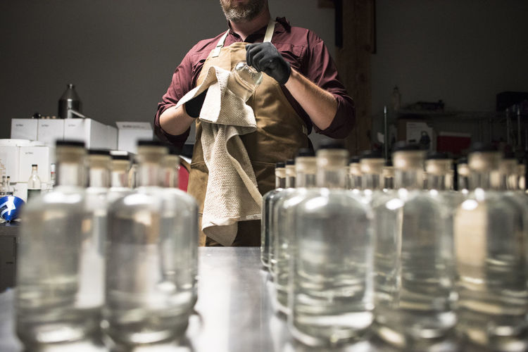 Midsection of man standing in glass bottles