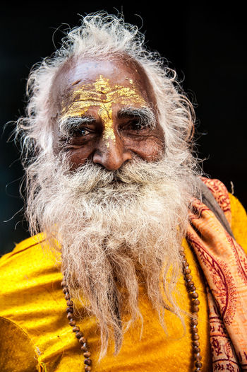 A happy old Indian Sadhu, or holy man, smiles at my camera near Mathura, between Agra and New Delhi in in Uttar Pradesh, India. He's attending one of the many celebrations held in the region every year to celebrate holi, a Hindu spring festival. Faith Happiness Hindu Hinduism Holy Man Indian Indian Culture  Old Man Sadhu Spirituality Wisdom Beard Belief Candid Holi Portrait Religion Smile Smiling Uttar Pradesh White Beard White Hair Wisdom Wise Yellow