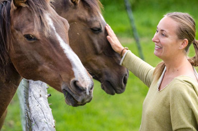 Smiling woman touching horse