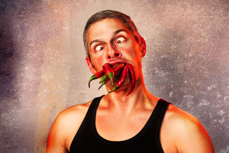 Close-Up Of Man Eating Red Chili Peppers By Wall
