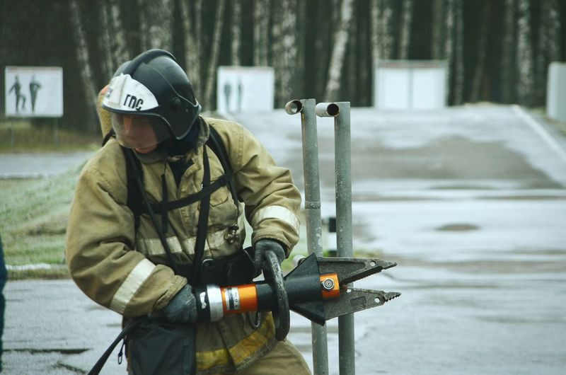 Firefighter holding equipment while standing on road