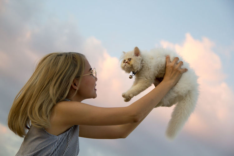 Young woman lifting cat against sky