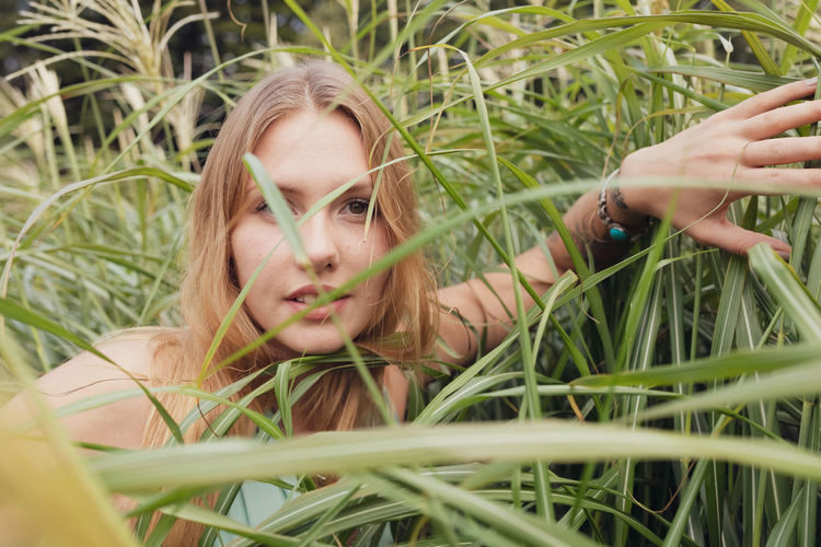 Portrait of woman seen through plants standing on land