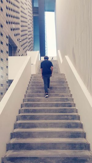 Rear view of boy walking upstairs