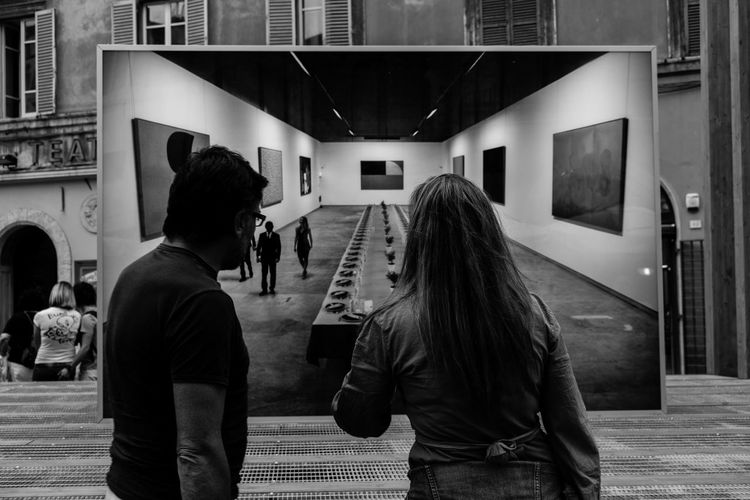 Monochrome Photography watching, by Claudia Ioan City Life Leisure Activity Rear View Togetherness The Roll Urbanphotography Urban People Photography Streetphotography Street Photography Perugia Embrace Urban Life Art Is Everywhere The Art Of Street Photography