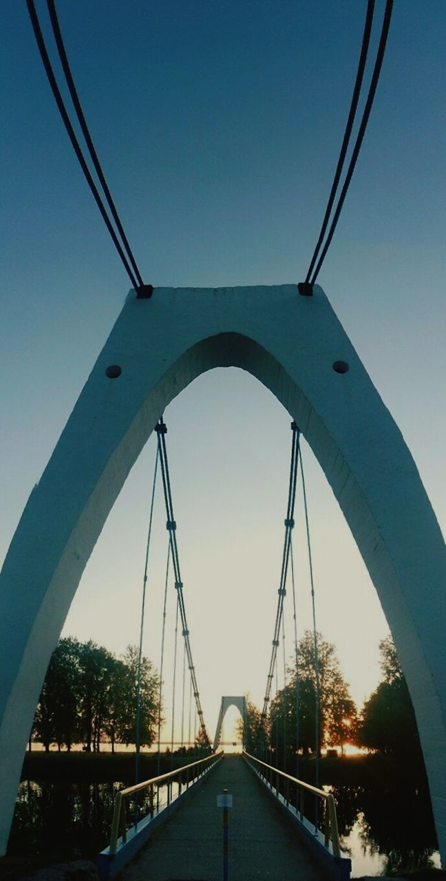bridge - man made structure, connection, engineering, architecture, built structure, clear sky, arch, transportation, outdoors, bridge, road, the way forward, day, suspension bridge, low angle view, sky, covered bridge, no people, footbridge, tree, city