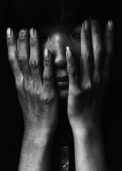 Close-up of young woman touching her face in dark