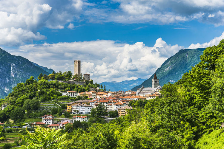 Panoramic view of townscape by mountains against sky