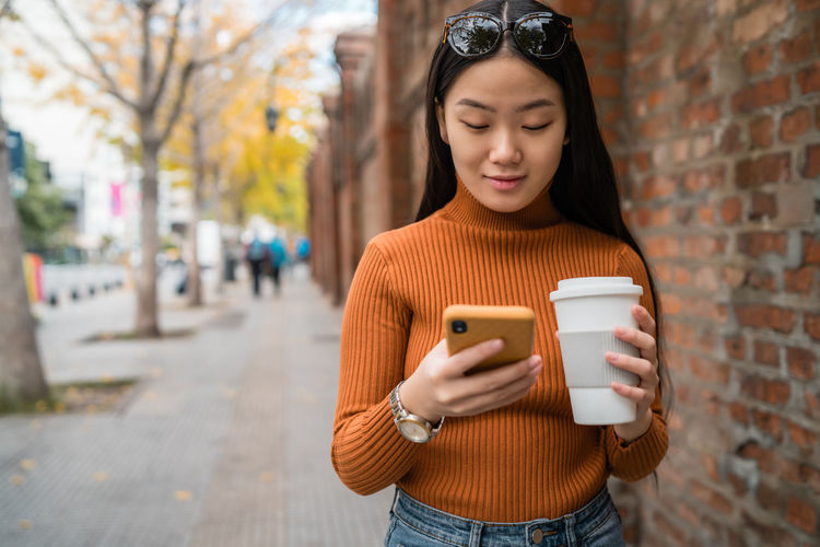 Woman using mobile phone while holding coffee cup on footpath