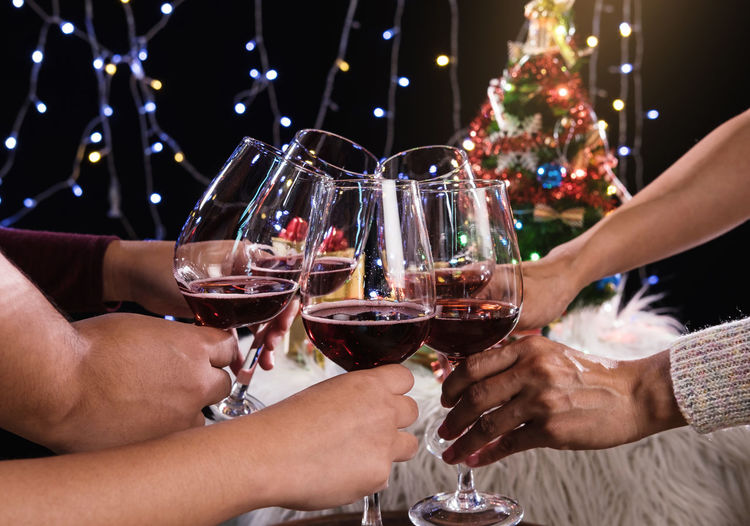 Midsection of friends toasting wineglasses during christmas