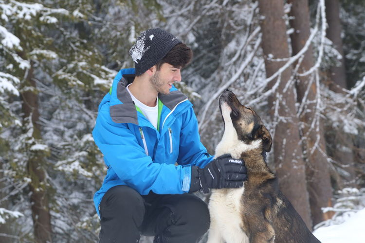 Young male petting a dog in the snow near the forest. Animal Themes Bonding Cold Temperature Day Dog Domestic Animals Friendship German Shepherd Happiness Leisure Activity Lifestyles Mammal Nature One Animal One Person Outdoors Pets Real People Side View Sitting Smiling Snow Warm Clothing Winter Young Adult