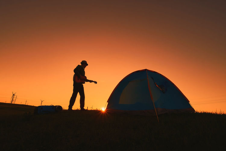 Man playing guitar by tent against sky during sunset
