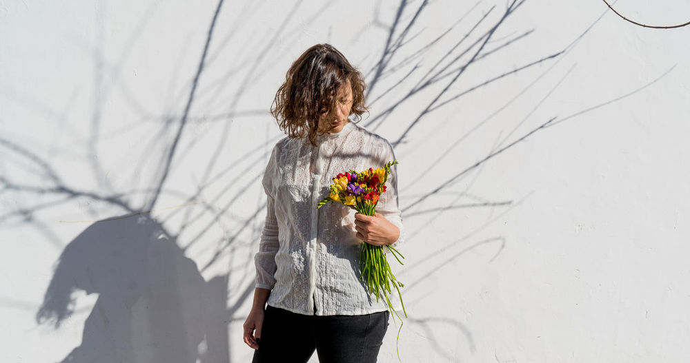 Woman holding a bunch of colorful flowers casting shadow on white wall