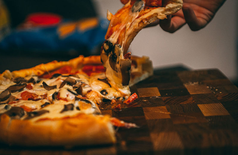 Close-up of hand holding pizza
