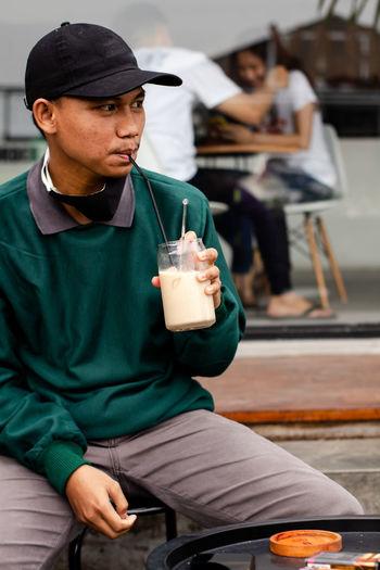Man holding drink sitting on seat