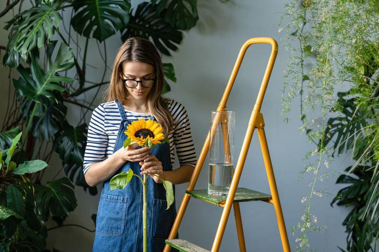 Smiling florist holding sunflower standing at flower shop