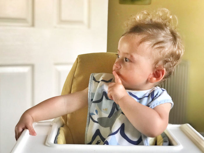 Cute baby girl looking away while sitting on high chair at home