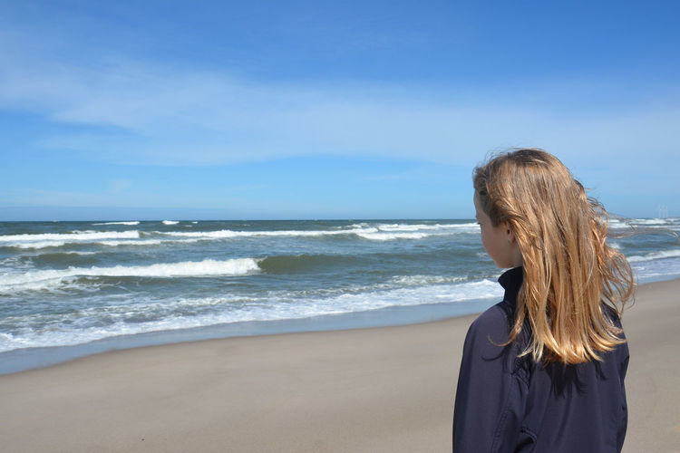 Rear view of girl standing at beach against blue sky