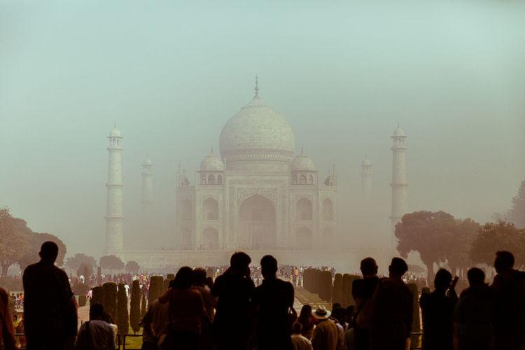 Crowd enjoying view of taj mahal during foggy weather