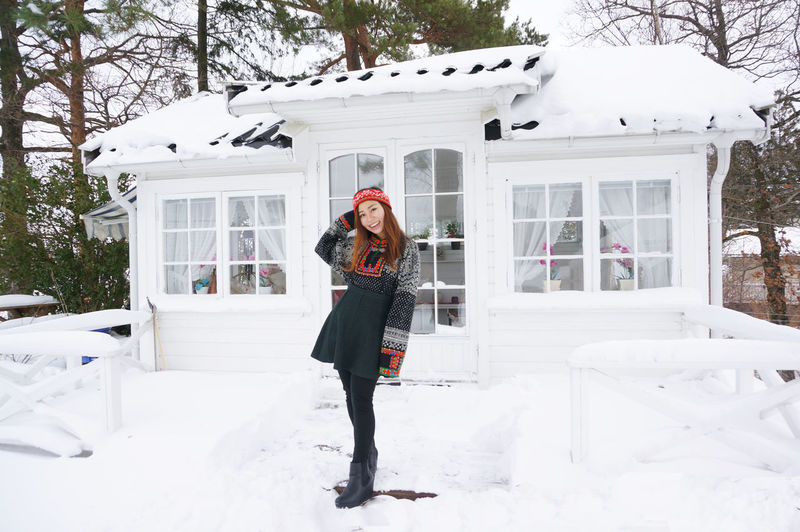 Full length portrait of young woman standing on snow covered house