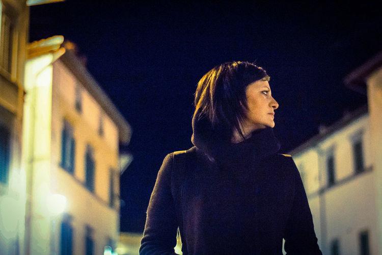 Woman looking at illuminated building in city at night