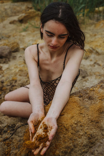 Young woman holding sand