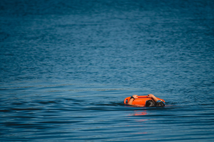 Water Sea Waterfront Day Nature Floating On Water Safety Floating Outdoors Life Jacket Tranquil Scene Orange Color One Person Beauty In Nature Blue Tranquility Rippled Inflatable