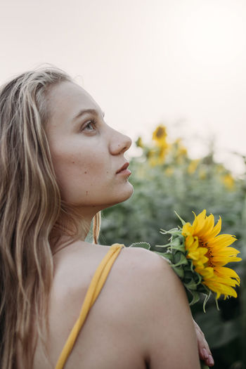 Portrait of woman with yellow flowers against blurred background