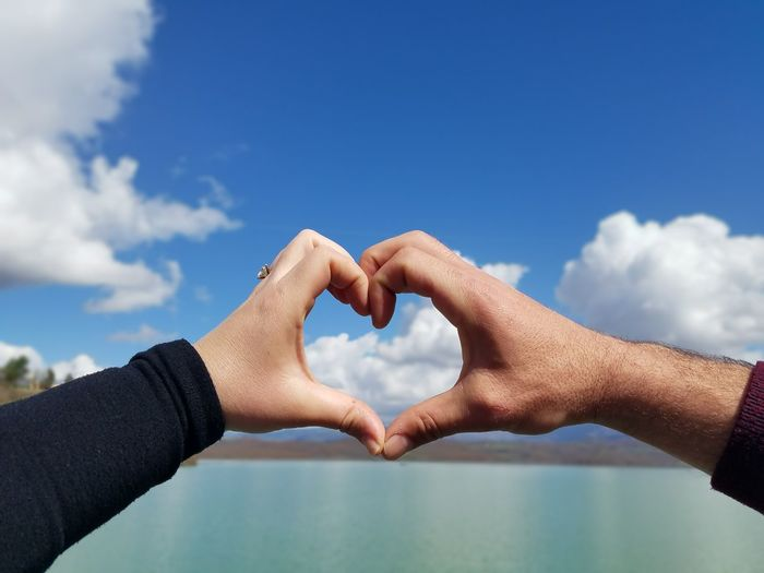 Cropped hands of couple making heart shape over lake against sky