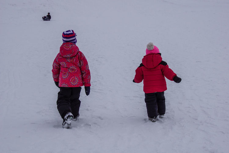 Rear view of siblings walking on snow covered field