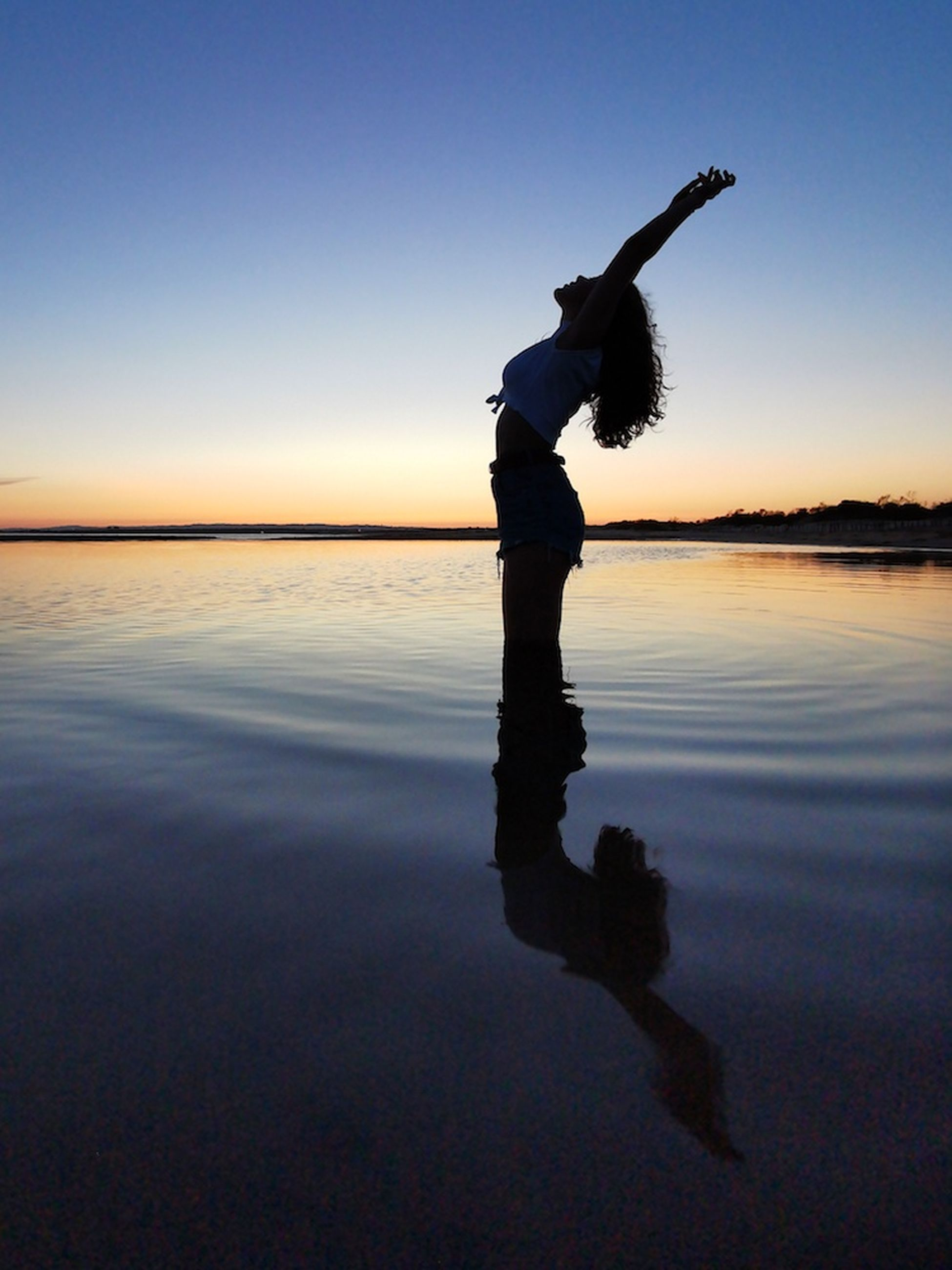 sky, water, sunset, real people, one person, reflection, silhouette, lifestyles, leisure activity, sea, nature, human arm, women, beauty in nature, beach, tranquility, full length, copy space, standing, arms raised, outdoors