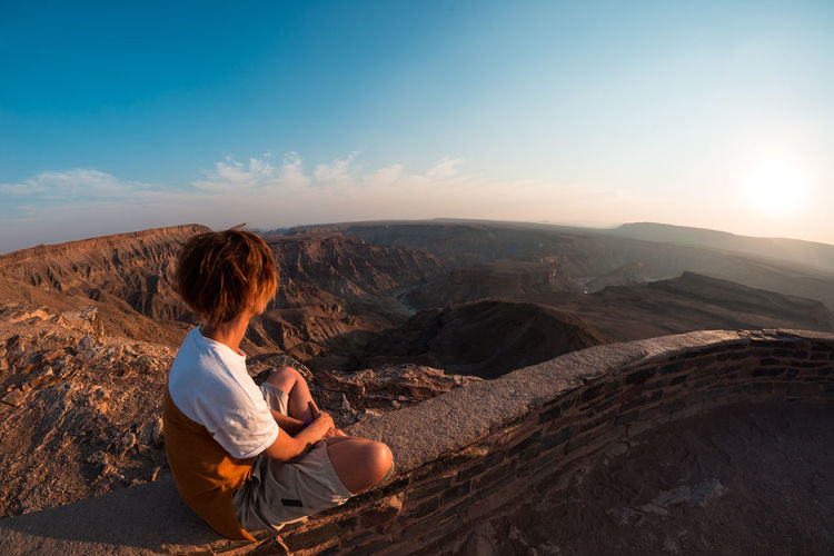 One person looking at the Fish River Canyon, scenic travel destination in Southern Namibia. Expansive view at sunset. Wanderlust traveling people. Keywords: fish river canyon,one person,looking at view,river,canyon,real people,expansive,people traveling,summer,namibia,travel destinations,valley,Landscape,cliff,sightseeing,vacation,desert,top,adventure,female,travel,mountains,exploration,summit,scenic,tourism,outdoors,panorama,landmark,majestic,above,famous,scenics,panoramic,wide-angle,clear sky,sunlight,viewpoint,idyllic,national park,horizon,remote,tourist,highland,relaxation,africa,happiness,extreme terrain Adult Beauty In Nature Environment Hair Hairstyle Leisure Activity Lifestyles Looking At View Mountain Mountain Range Nature Non-urban Scene One Person Outdoors Real People Rear View Rock Rock - Object Scenics - Nature Sitting Sky Tranquil Scene Tranquility