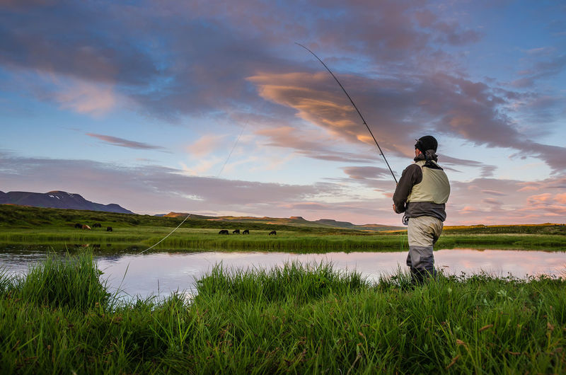 Rear view of man fishing on lake