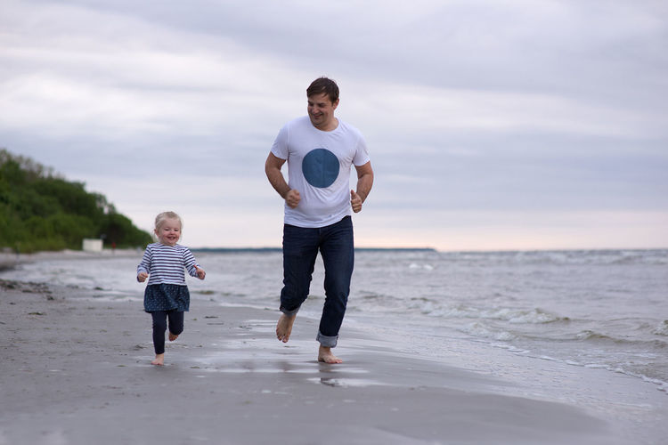 Father and daughter playing at beach against sky