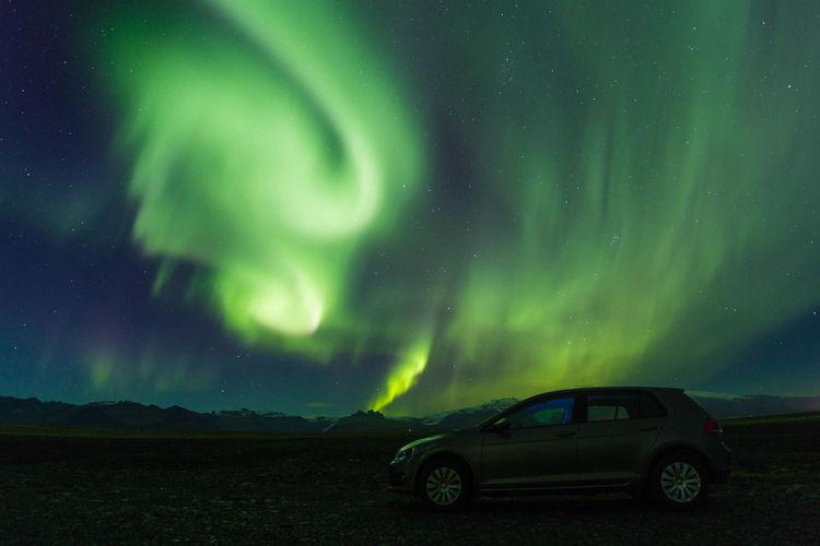 Cars on illuminated landscape against sky at night