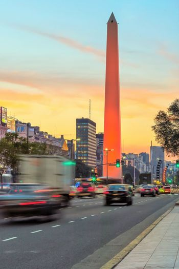 Obelisk This Is Latin America Blurred Motion Building Building Exterior Built Structure Car City Land Vehicle Mode Of Transportation Motion Motor Vehicle No People Obelisco, Buenos Aires 🌆 Office Building Exterior on the move Outdoors Road Sky Skyscraper Street Sunset Tall - High Transportation
